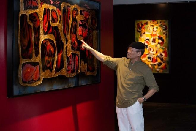 Họa sỹ Ngô Xuân Bính trước một bức tranh của ông