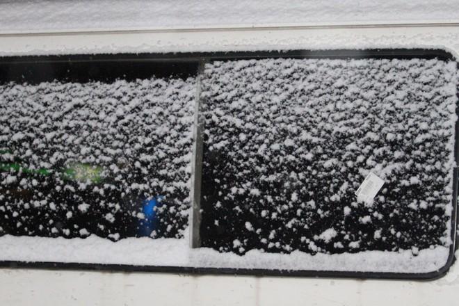 Tuyết rơi dày, phủ kín một cánh cửa xe ô tô (Ảnh: Hoàng Linh)