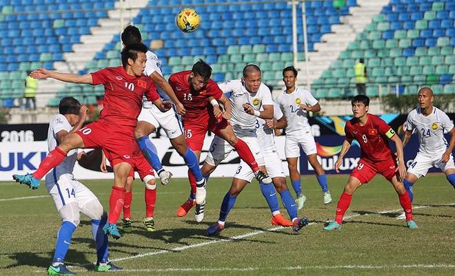 Văn Quyết (số 10) trong một pha bật cao đánh đầu trong vòng cấm Malaysia