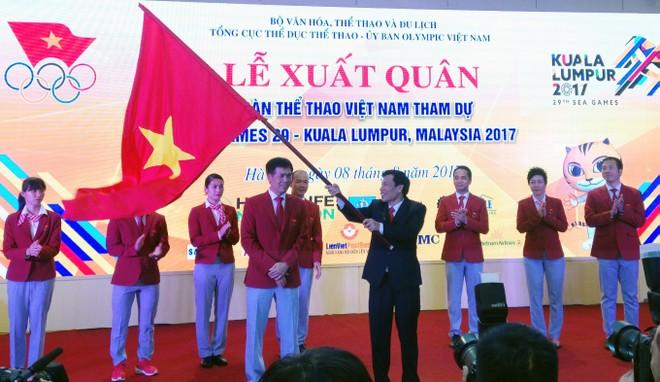 Bộ trưởng Bộ VH-TT&DL Nguyễn Ngọc Thiện (áo vest đen) trao cờ Tổ quốc cho Trưởng đoàn Thể thao Việt Nam Trần Đức Phấn cùng lời chúc giành thành tích cao nhất tại SEA Games 29