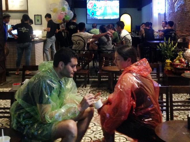 Hai du khách nước ngoài thờ ơ với chiếc màn hình máy chiếu đang phát trực tiếp trận khai mạc World Cup 2018