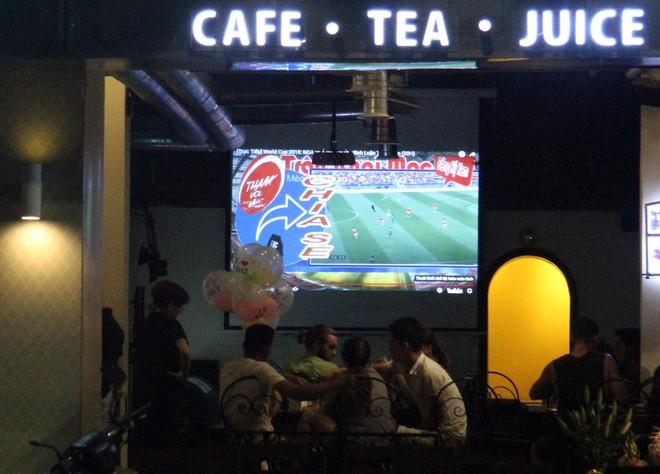 Một nhóm người Việt Nam và cả người nước ngoài theo dõi trận khai mạc World Cup 2018 tại một quán giải khát trên phố Hàng Khay