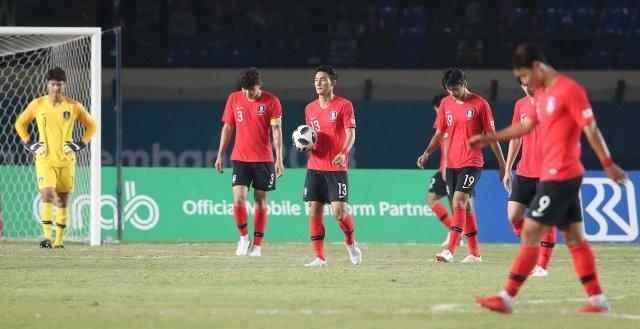 Các cầu thủ Hàn Quốc cúi đầu buồn bã rời sân sau trận thua