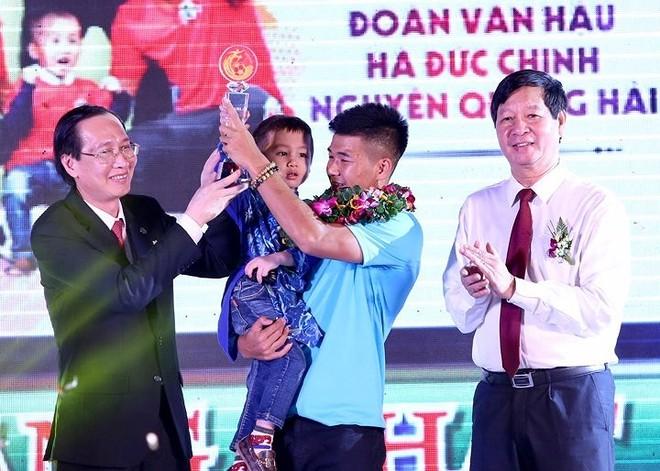 Đức Chinh - đại diện nhóm cầu thủ, cùng bé Tom trên bục nhận giải Fair-play 2018