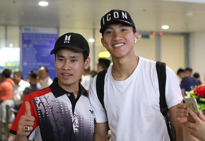 Văn Hậu tươi cười chụp ảnh cùng người hâm mộ tại sân bay Nội Bài, dù vừa trải qua hành trình di chuyển dài mệt mỏi (Ảnh: Zing)