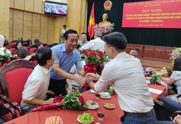 Ông Đỗ Viết Bình, Chủ tịch UBND quận Ba Đình tặng hoa chúc mừng các doanh nghiệp