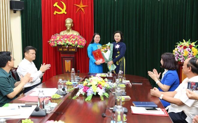 Phó Bí thư Thường trực Thành ủy Ngô Thị Thanh Hằng trao quyết định và tặng hoa bà Phạm Hải Hoa