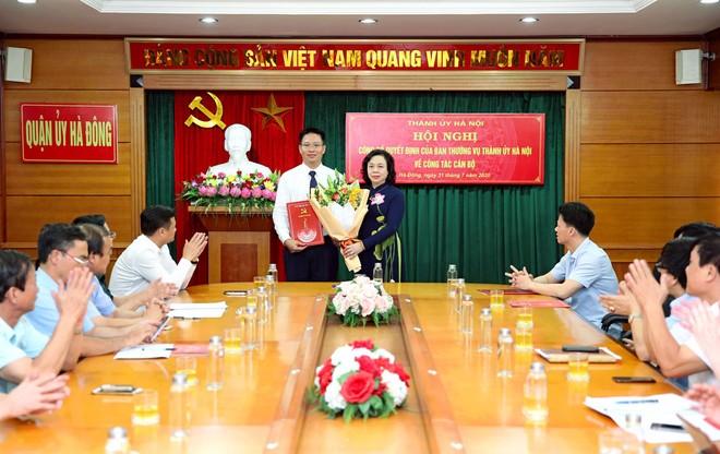 Phó Bí thư Thường trực Thành ủy Ngô Thị Thanh Hằng trao quyết định và tặng hoa ông Nguyễn Thanh Xuân
