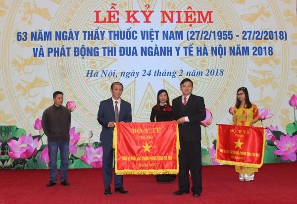 Ông Nguyễn Đình Anh (bên phải), Vụ trưởng Vụ Truyền thông thi đua khen thưởng - Bộ Y tế trao Cờ Thi đua của Bộ Y tế cho các tập thể, cá nhân thuộc Sở Y tế Hà Nội