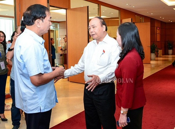 Thủ tướng Nguyễn Xuân Phúc trao đổi với các đại biểu bên hành lang Quốc hội