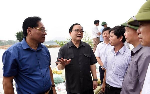 Chủ tịch UBND huyện Chương Mỹ Đinh Mạnh Hùng (ngoài cùng bên trái) lắng nghe chỉ đạo của Bí thư Thành ủy tại buổi kiểm tra đê Hữu Bùi