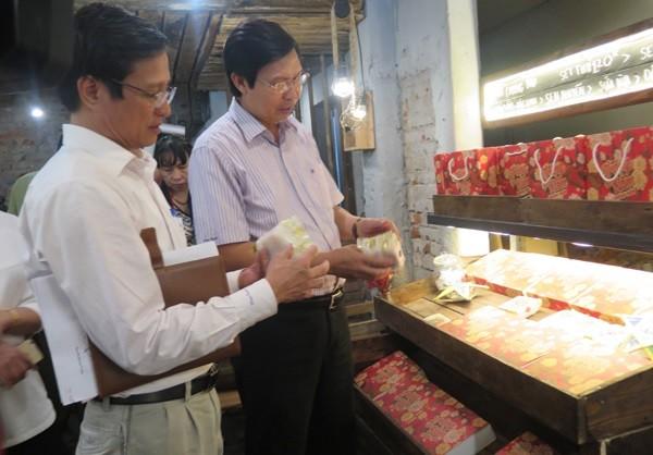 Phó Giám đốc Sở Y tế Hà Nội Trần Văn Chung (phía trong) kiểm tra ATTP tại một cơ sở sản xuất bánh Trung thu