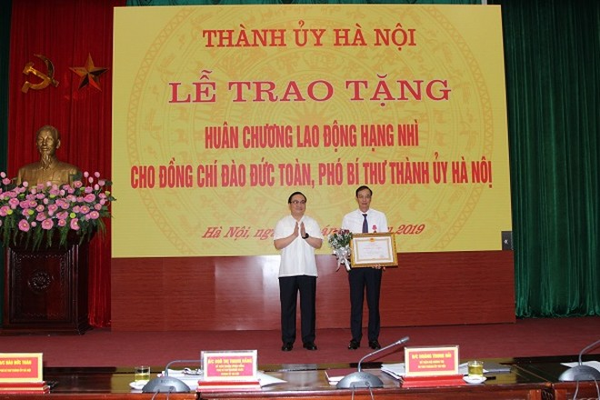 Bí thư Thành ủy Hoàng Trung Hải chúc mừng đồng chí Đào Đức Toàn được nhận Huân chương Lao động hạng Nhì