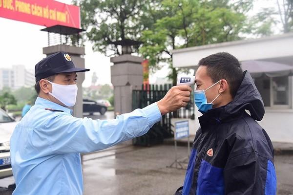Người dân được kiểm tra thân nhiệt khi đến trụ sở cơ quan ở quận Long Biên