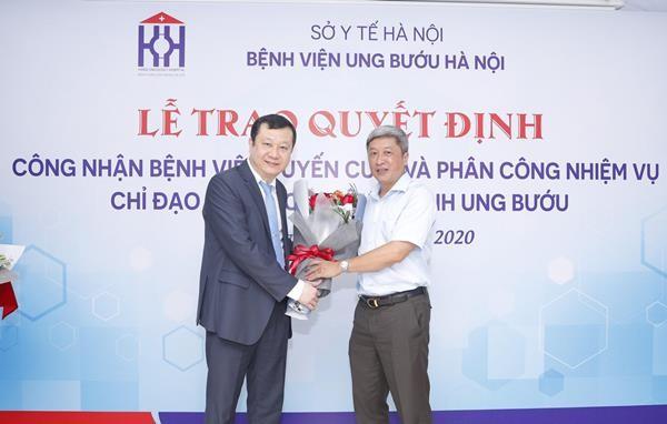 Thứ trưởng Bộ Y tế Nguyễn Trường Sơn (áo trắng) trao quyết định và chúc mừng Bệnh viện Ung bướu Hà Nội