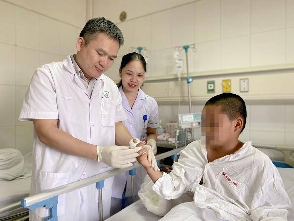 BS Đào Văn Giang khám lại ngón tay cho cháu bé sau khi được nối thành công