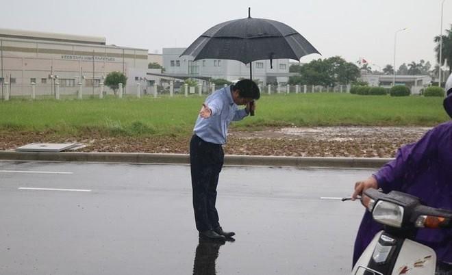 Tổng Giám đốc IQ 8 đứng dưới mưa cúi chào khách hàng vào đổ xăng