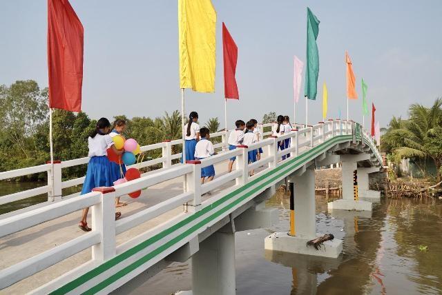 Có chiếc cầu mới, các em học sinh ở xã Phú Quới, huyện Long Hồ, Vĩnh Long rút ngắn được quãng đường đến lớp. (Ảnh: Tất Đạt).