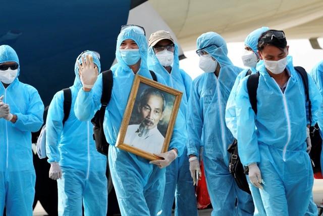 Những công dân Việt Nam tại Guinea Xích đạo đã mang theo ảnh Bác khi lên máy bay về nước