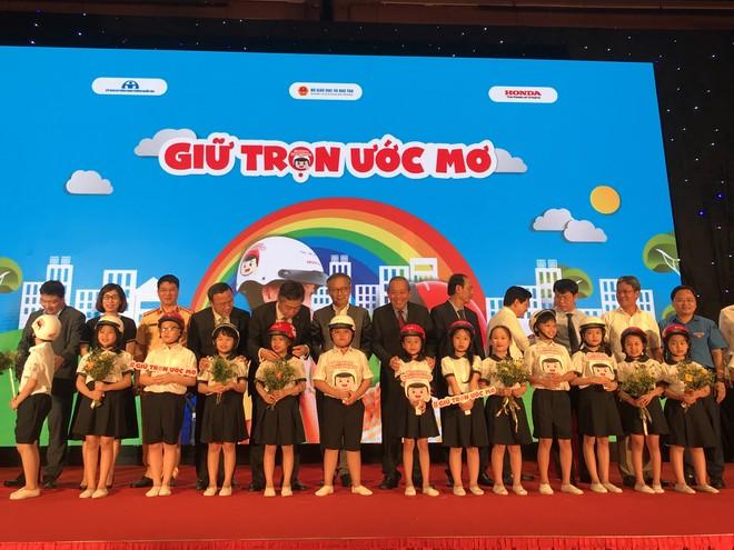 Đồng chí Trương Hòa Bình - Ủy viên Bộ Chính trị, Phó Thủ tướng Thường trực Chính phủ, Chủ tịch Ủy ban ATGTQG cùng đại diện các Bộ và Công ty Honda Việt Nam trao tặng mũ bảo hiểm cho các em học sinh