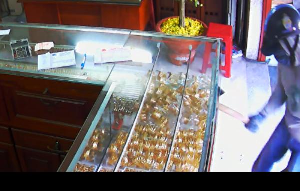 Camera an ninh của tiệm vàng ghi nhận lại cảnh Thắng dùng búa đập tủ kính, cướp vàng. Ảnh trích xuất từ camera an ninh của tiệm vàng