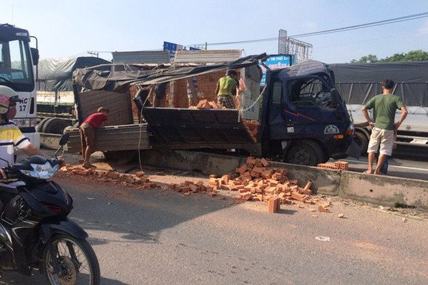 Xe tải chở gạch lật nghiêng sau cú tông xe khách