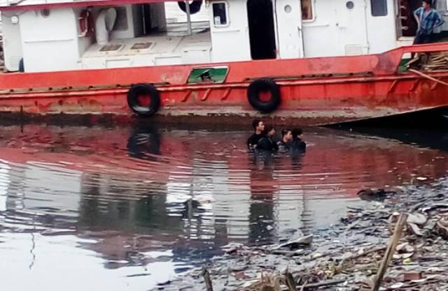 Thợ lặn đưa thi thể nạn nhân lên bờ. Ảnh: Minh Thư.