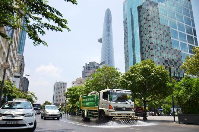 """Xe chuyên dụng Công ty dịch vụ công ích quận 1 phun nước """"giải nhiệt"""" mặt đường phố đi bộ Nguyễn Huệ, quận 1."""
