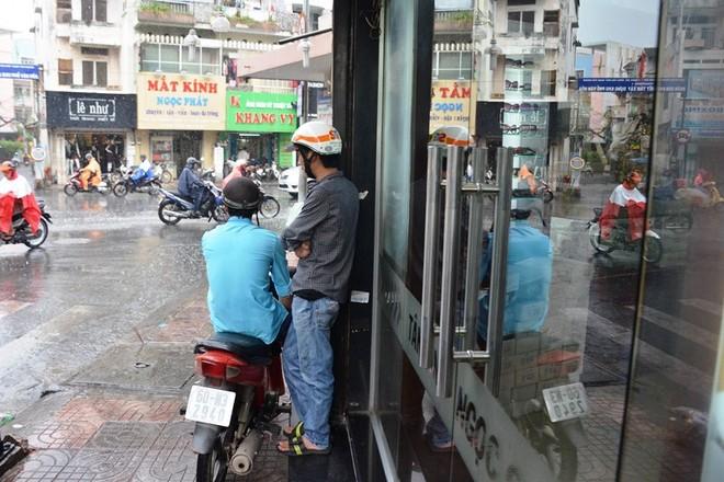 Nhiều người đi đường vội tấp vào vỉa hè để trú khi cơn mưa đổ ào xuống.