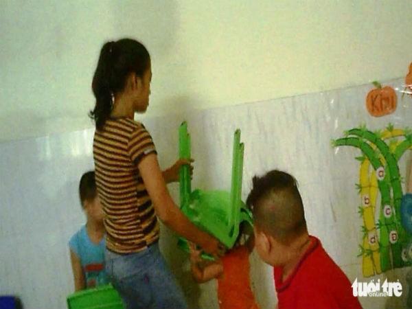 1 bảo mẫu dùng ghế nhựa đè lên đầu 1 đứa trẻ. Ảnh: Báo Tuổi Trẻ