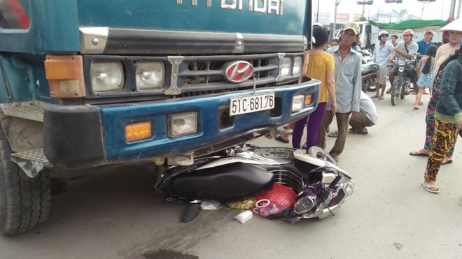 Chiếc xe máy nằm trọn dưới gầm xe ben