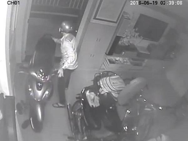 Tên trộm dắt chiếc xe máy của chủ nhà. Ảnh cắt từ clip.