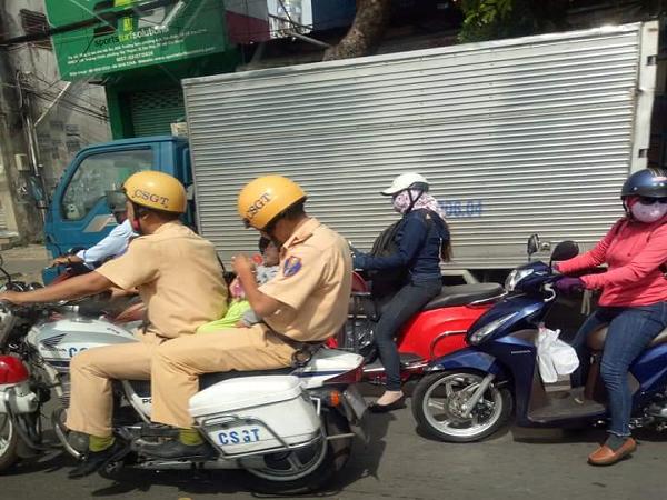 CSGT vỗ về cháu bé trên mô tô đặc chủng trên đường đi đến bệnh viện.