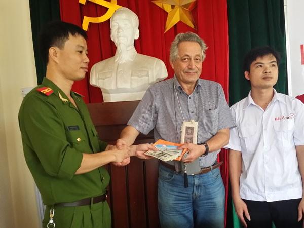 Cơ quan công an và anh Vũ Văn Kiên trao trả lại tài sản cho vị khách nước ngoài