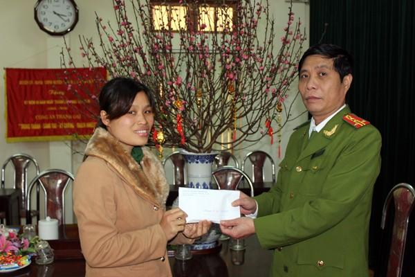 Đại tá Đinh Công Dụng - Trưởng CAH Thanh Oai trao tặng số tiền ủng hộ cho chị Nguyễn Thị Nga