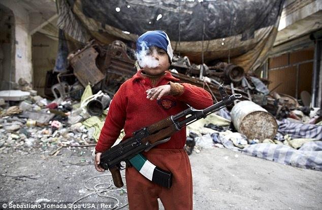 Sốc với hình ảnh chiến binh 7 tuổi khoác AK-47, phì phèo thuốc lá ảnh 1