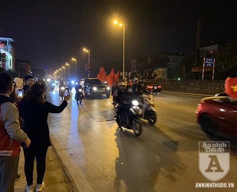 Chào mừng đoàn xe chở 2 đội tuyển bóng đá Việt Nam trở về, nhiều người hâm mộ đã theo sau hộ tống, hòa cùng niềm phấn khởi của người dân hai bên đường. Ảnh: Nguyễn Quốc Dũng
