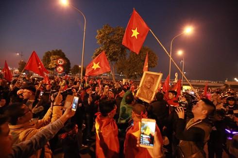 Người dân mang cờ hoa cùng ảnh HLV Park Hang-seo đến chờ đón những người hùng của thể thao Việt Nam. Ảnh: Lam Thanh
