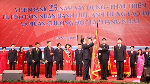 Thủ tướng Chính phủ Nguyễn Tấn Dũng gắn Huân chương Độc lập hạng Nhất lên lá cờ truyền thống của VietinBank
