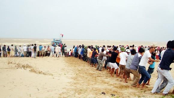 Hàng trăm người kéo tàu bị nạn vào bờ ảnh 1