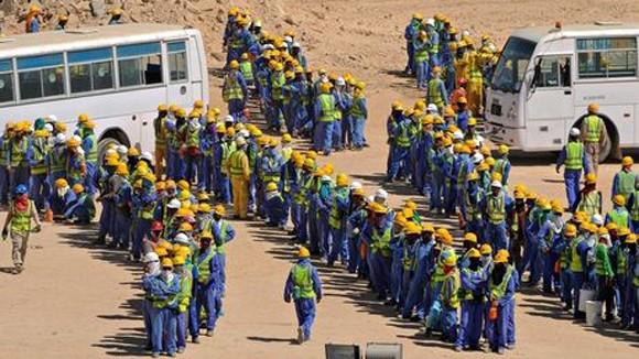 Lao động nhập cư xếp hàng lên xe buýt trở về chỗ ở, tại một SVĐ phục vụ World Cup 2022 ở Qatar